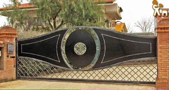 Originale porta d'ingresso alla proprietà in forma di occhio nella parte superiore e diagonali nella parte inferiore