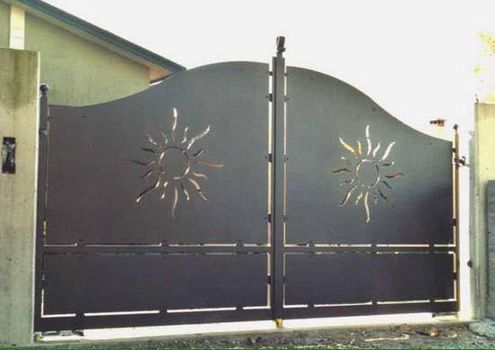 Originale porta d'ingresso alla proprietà, curvo  nella parte superiore e un sole su ciascun foglio