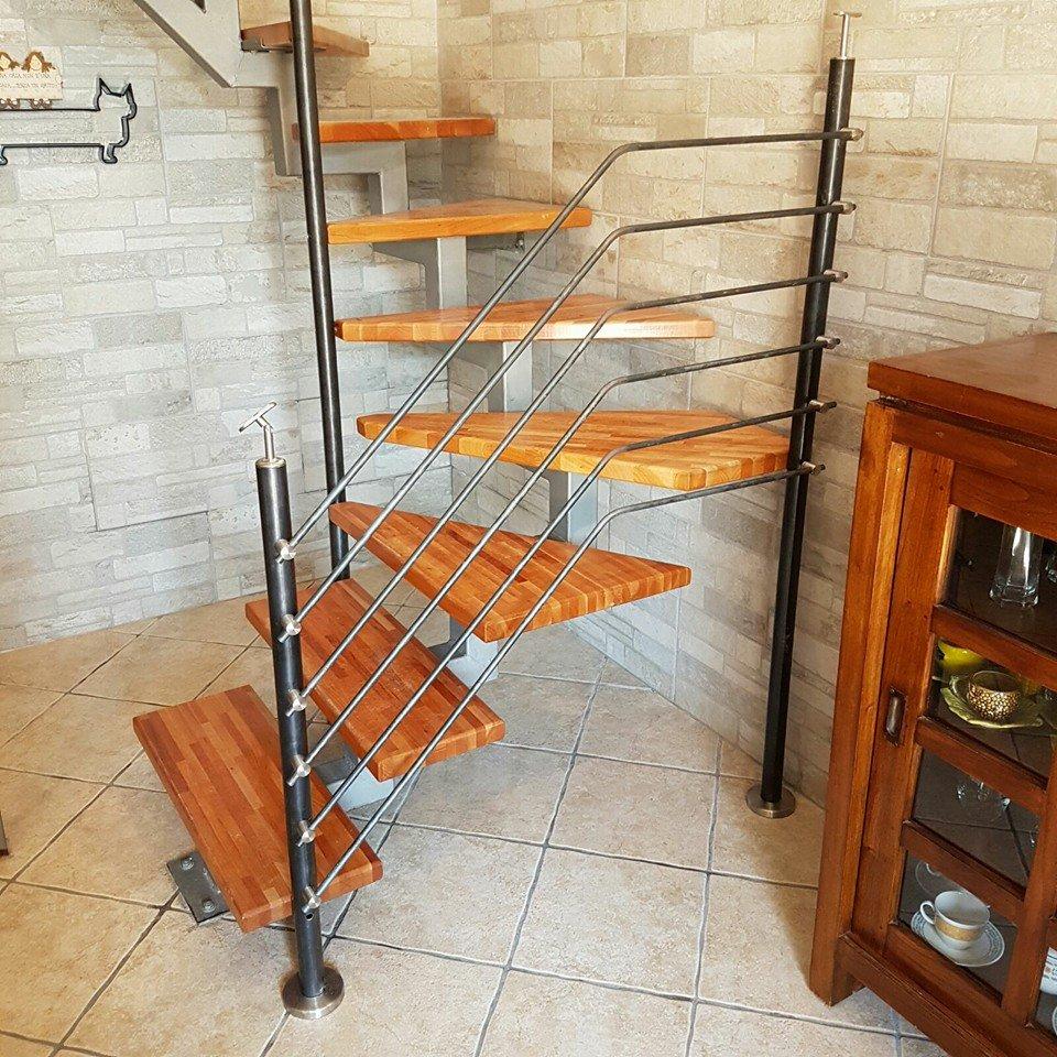 Scala interna a spirale con gradini di legno all'aria e ringhiera in ferro