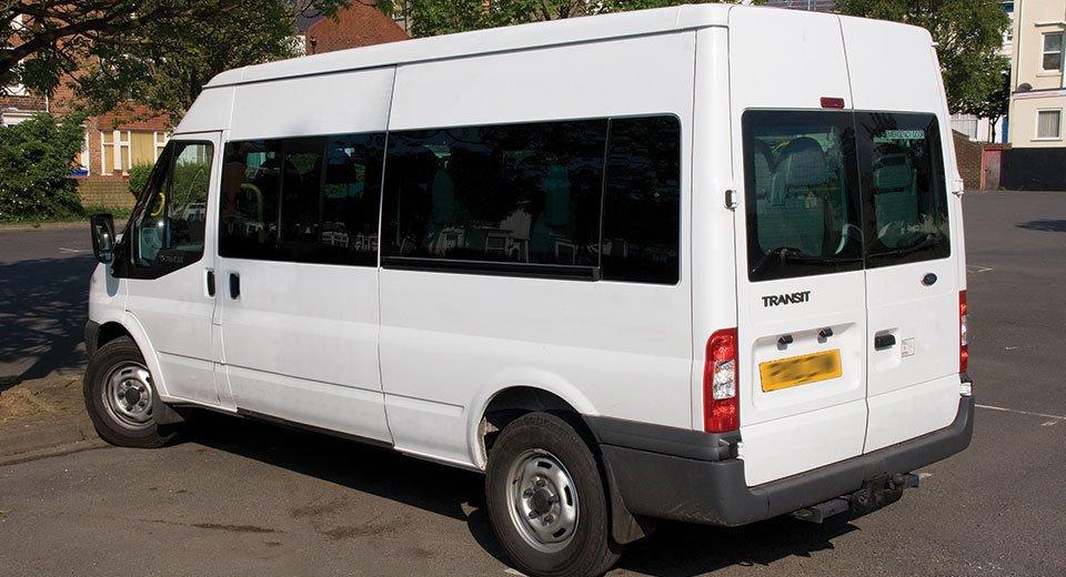 A white minibus in a car park