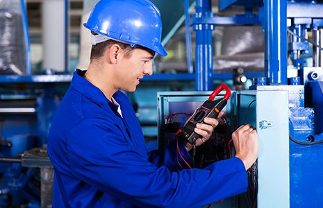 Technician examining control box with digital insulation tester