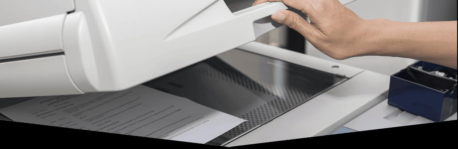 mano di donna che solleva il pannello superiore di una stampante