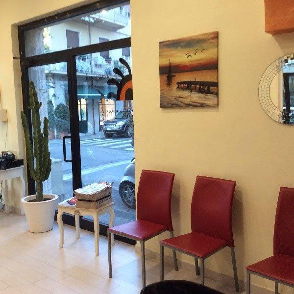 delle sedie bordeaux, un tavolino con delle riviste e una pianta con un cactus vicino all'entrata
