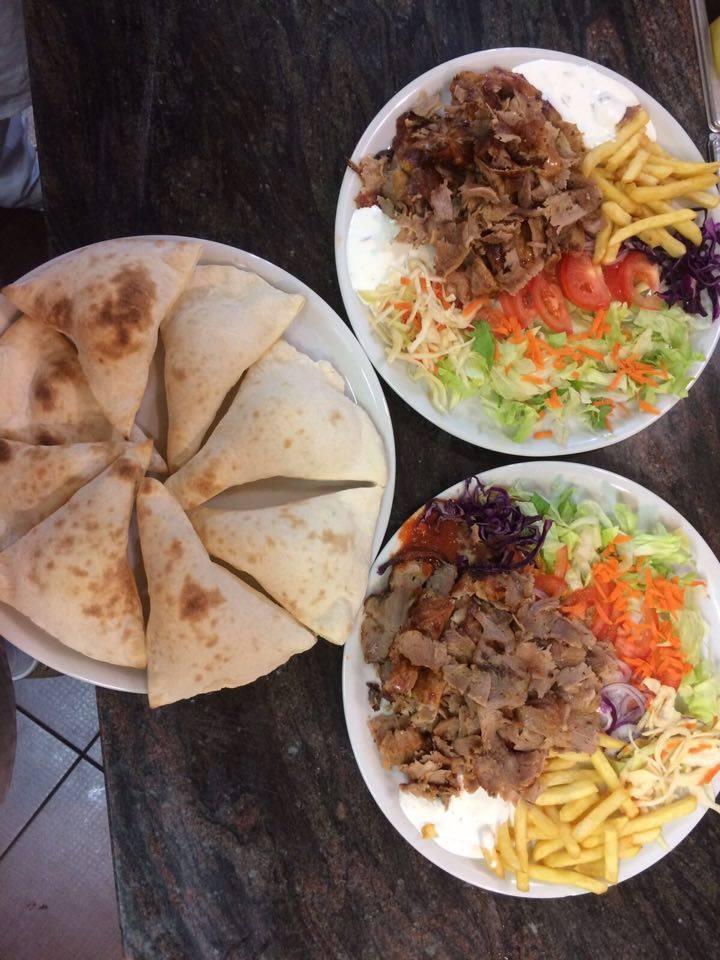 Due piatti di kebab e un piatto di pita