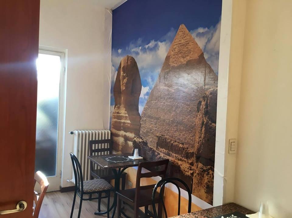 Interno del locale con tavolino e parete con poster di una sfinge e una piramide