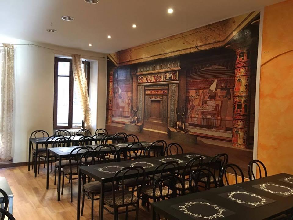 Interno del locale con eleganti tavolini e pareti con motivi egiziani