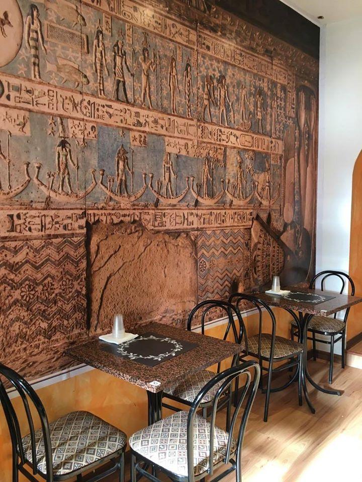 Tavolini interni di Pizza Speedy Cleopatra con parete a motivi egiziani