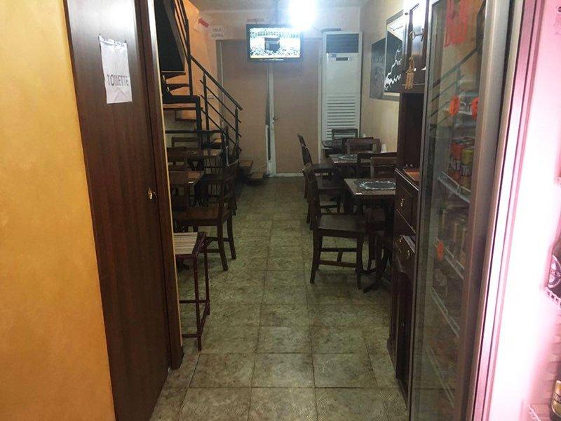 Un'entrata con vista dei tavoli all'interno di un ristorante e una tv al muro