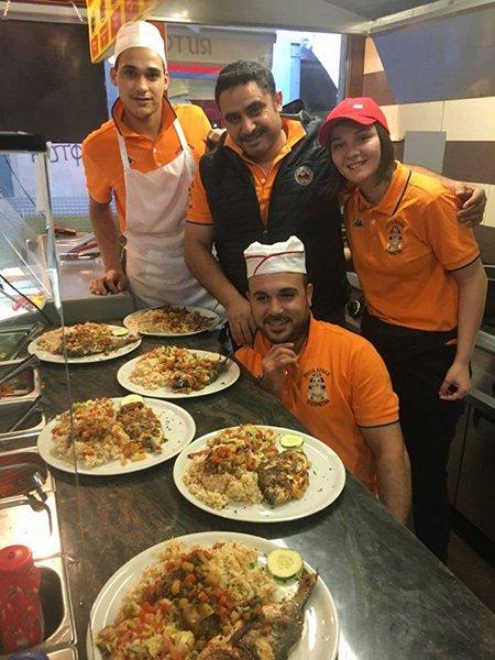 cuochi e camerieri vestiti di arancione in una cucina e vicino dei piatti di risotto e del pesce