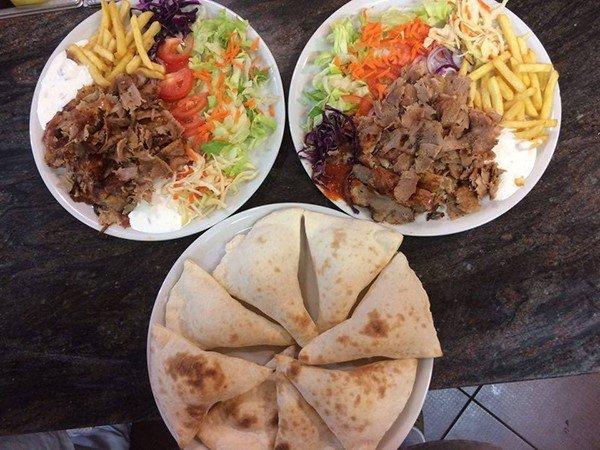 un piatto di piccoli calzoni e altri due piatti con kebab,insalata,pomodori e patatine fritte