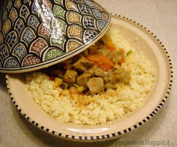un piatto di cous cous con carne carote e verdure