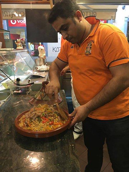 un uomo con una maglietta arancione che sta per prendere una pentola con dentro del cous cous alla carne e verdure
