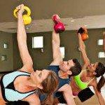 delle persone in palestra che fanno degli esercizi con dei pesi colorati
