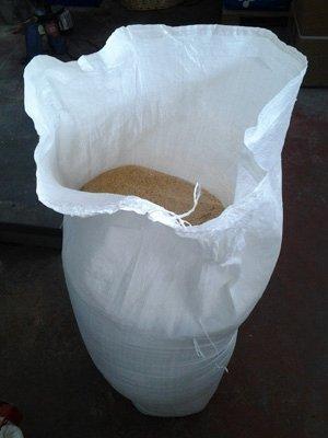 un sacco bianco con dentro un prodotto in polvere marron chiaro