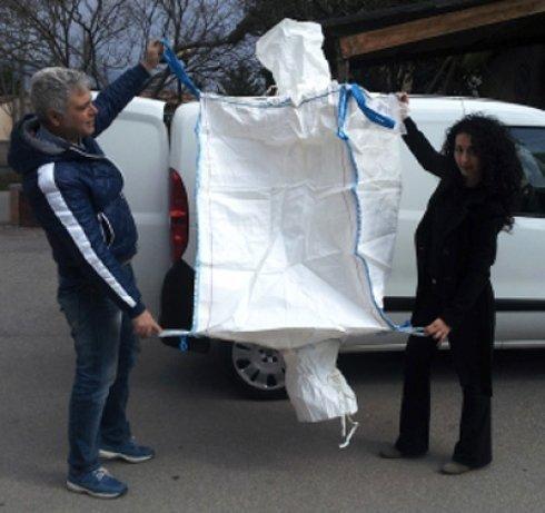 un uomo e una donna mentre mostrano una borsa ecologica aperta