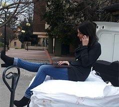 due foto, nella prima un uomo sta trainando un carrello con delle borse e una donna seduta e nella seconda la stessa donna e' al telefono mentre siede sul carrello