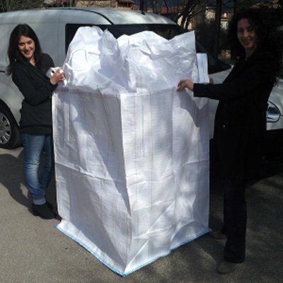 due donne con i capelli neri davanti a un furgone bianco mostrano una borsa ecologica