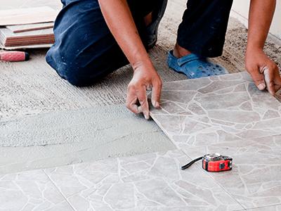 muratore sistema delle piastrelle nel pavimento