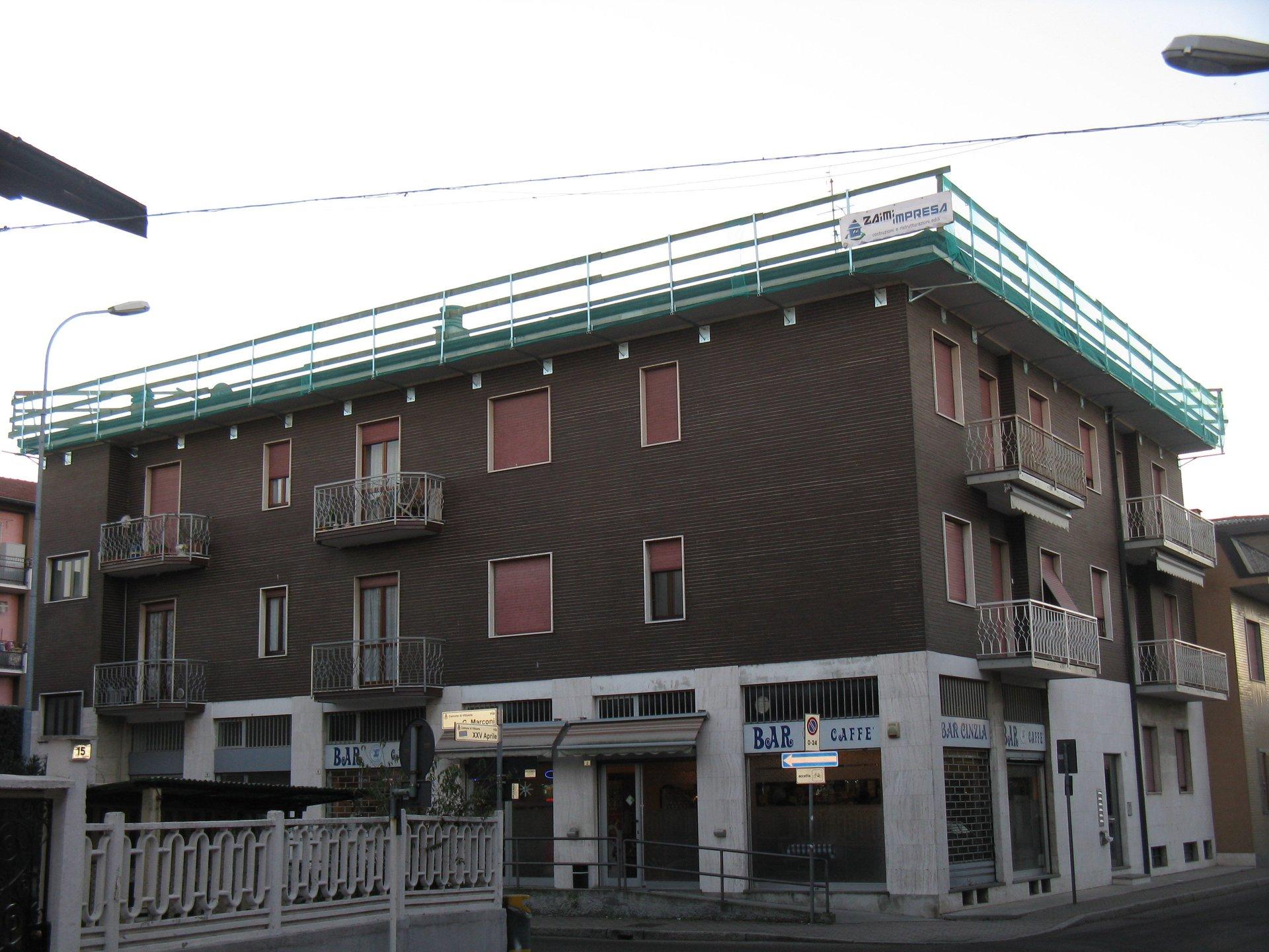 vista esterna di un edificio con parete in legno, balconi e finestre