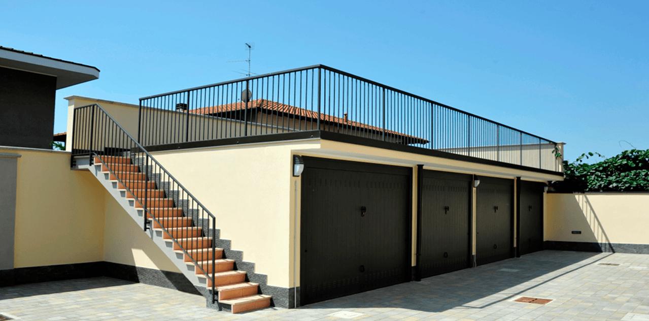 scala esterna e tetto di una casa con ringhiere in ferro sfondo cielo blu