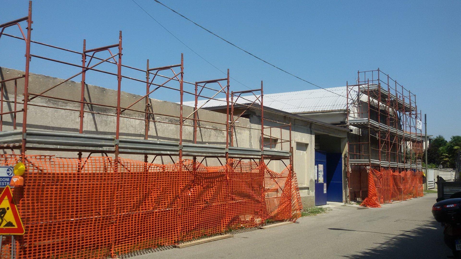 vista laterale di una casa durante costruzione con ponteggi