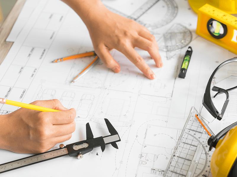 Una mano con una matita che disegna su un progetto edile e degli attrezzi