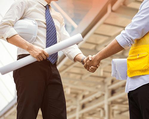 stretta di mano tra un ingegnere e un tecnico di un cantiere