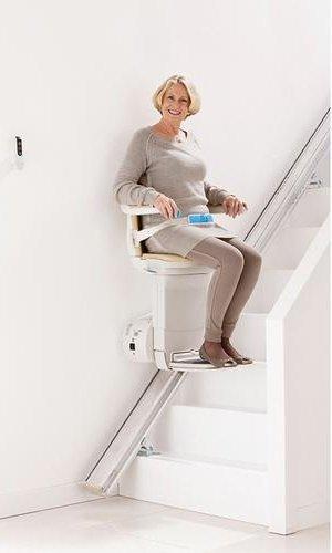 donna mentre sale le scale con una poltrona montascale