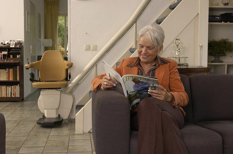 donna seduta sul divano mentre legge il giornale e dietro una poltrona montascale