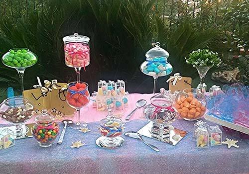Tavola estera con diverse coppe e recipienti di vetro pieni di dolci
