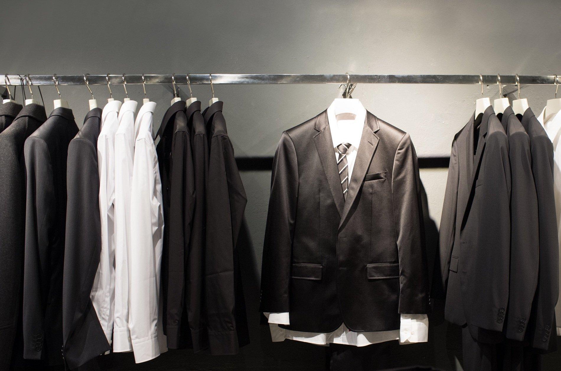 un appendino con delle camicie e dei completi di color nero