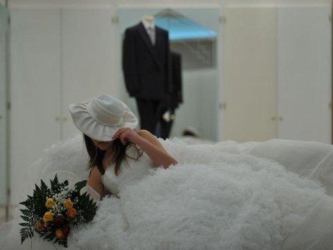un manichino con un abito da sposo e una sposa in posa con un bouquet di fiori in mano