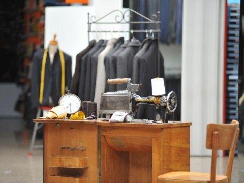un appendino con degli abiti da uomo e accanto una macchina da cucire