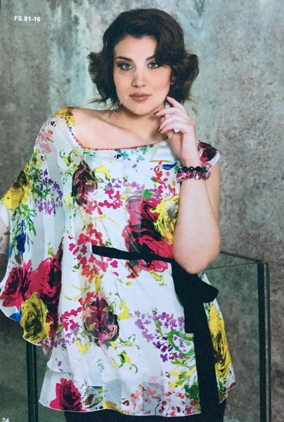 una donna con una camicetta  multicolore e una cintura nera