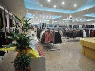 interno di un negozio di abbigliamento con degli appendini e delle giacche appese