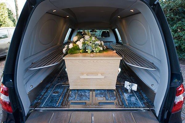 Ataud all'interno dell'automobile coperto di fiori bianche