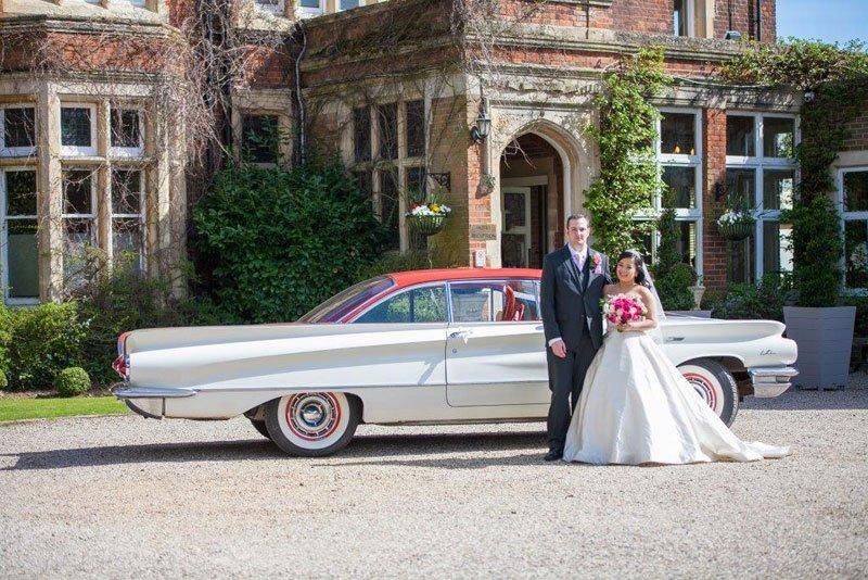 Newly married couple near a car