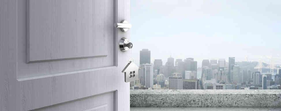 porta aperta che da su un balcone con vista su  grattacieli