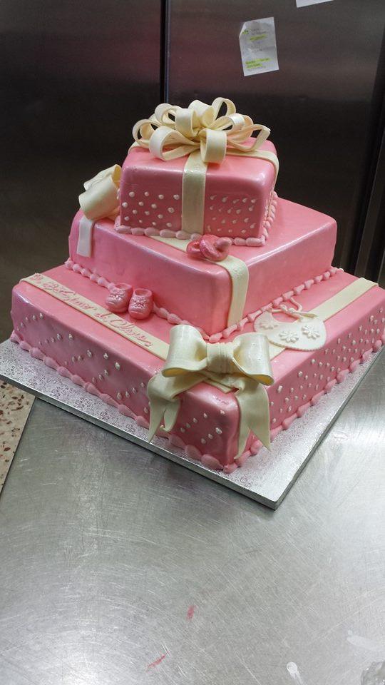 una torta di glassa rosa a tre piani a forma di pacco regalo