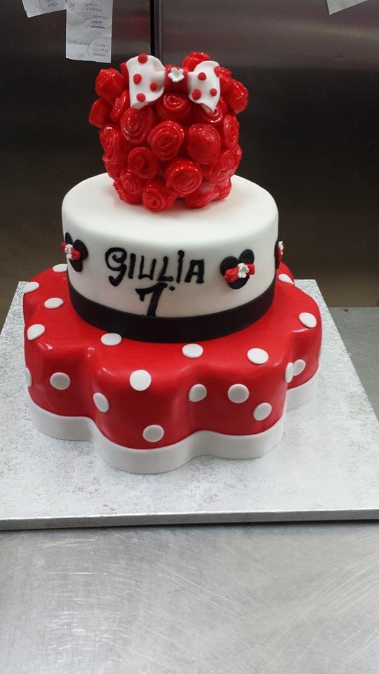 una torta a tre piani di glassa rossa a pois bianchi e bianca con un fiocco in cima e la scritta Giulia