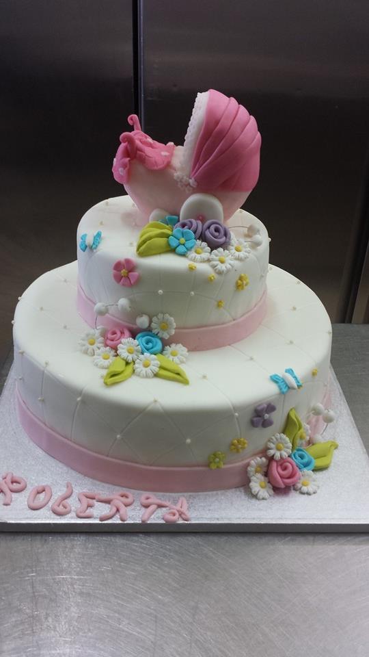 una torta a due piani di glassa bianca con fiori colorati e la scritta Roberta