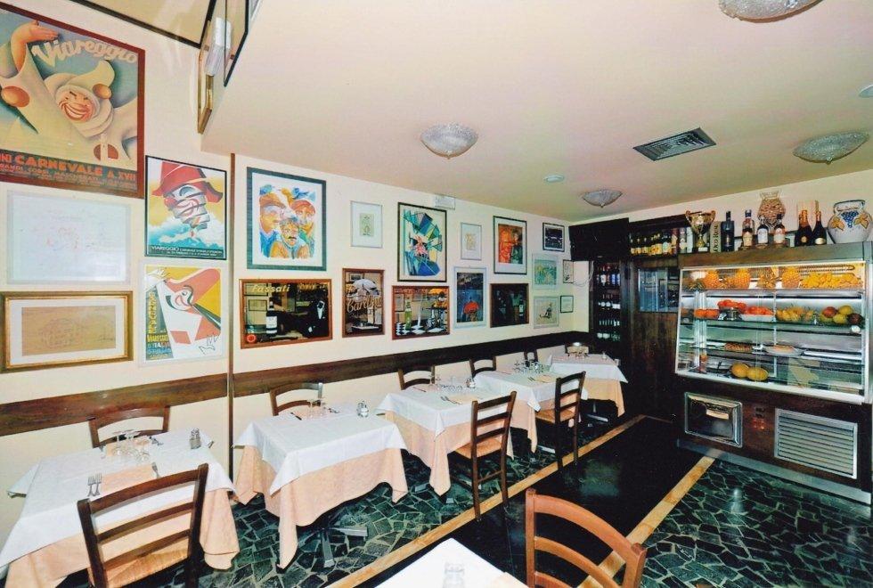 vista interna di una una ristorante con tavoli apparecchiati, arte su parete, banco frigo con arredamento
