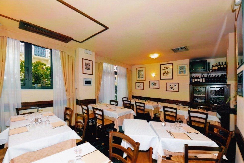 vista interna di una una ristorante con tavoli apparecchiati, parete decorata e tende trasparente e ben arredato