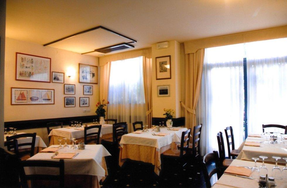 vista interna di una una ristorante con tavoli apparecchiati, parete decorata e tende trasparente