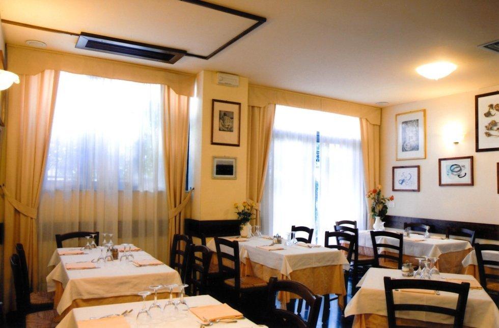 vista frontale di una una ristorante con tavoli apparecchiati, parete decorata e tende trasparente