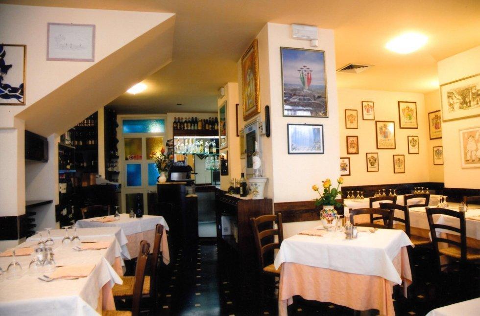 vista frontale di una una ristorante con tavoli apparecchiati, parete decorata e lampadina in soffitto