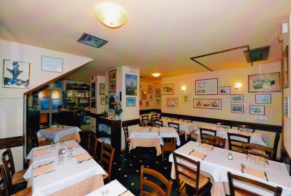 vista interna di una una ristorante con tavoli apparecchiati, parete decorata e lampadina in soffitto