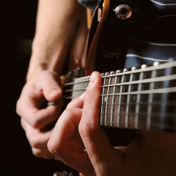 due mani che suonano una chitarra