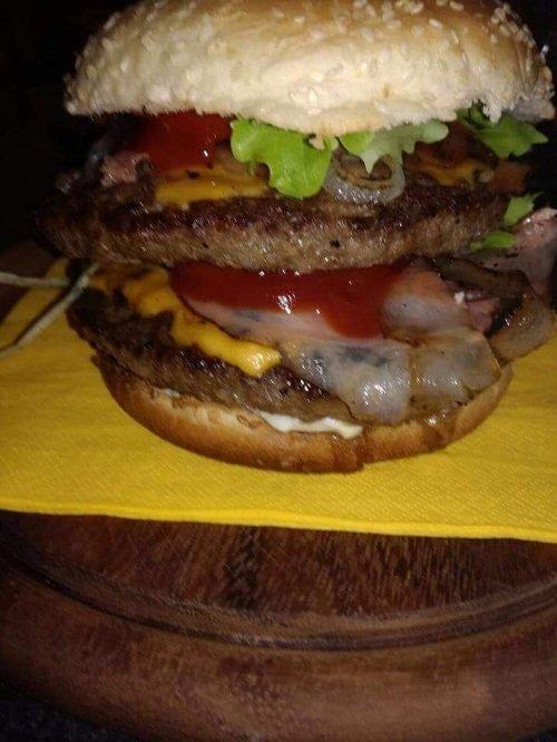 un panino con hamburger, ketchup,cipolle e formaggio