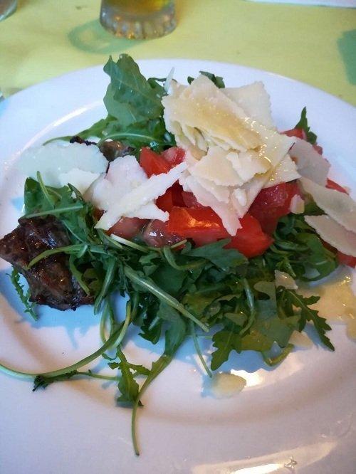 un piatto a base di carne, rucola,pomodori e grana